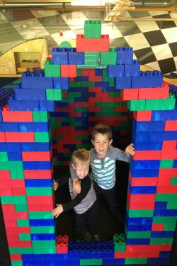 2 children posing in a house made of blocks