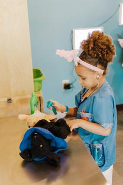 A child examining pet toys like a vet